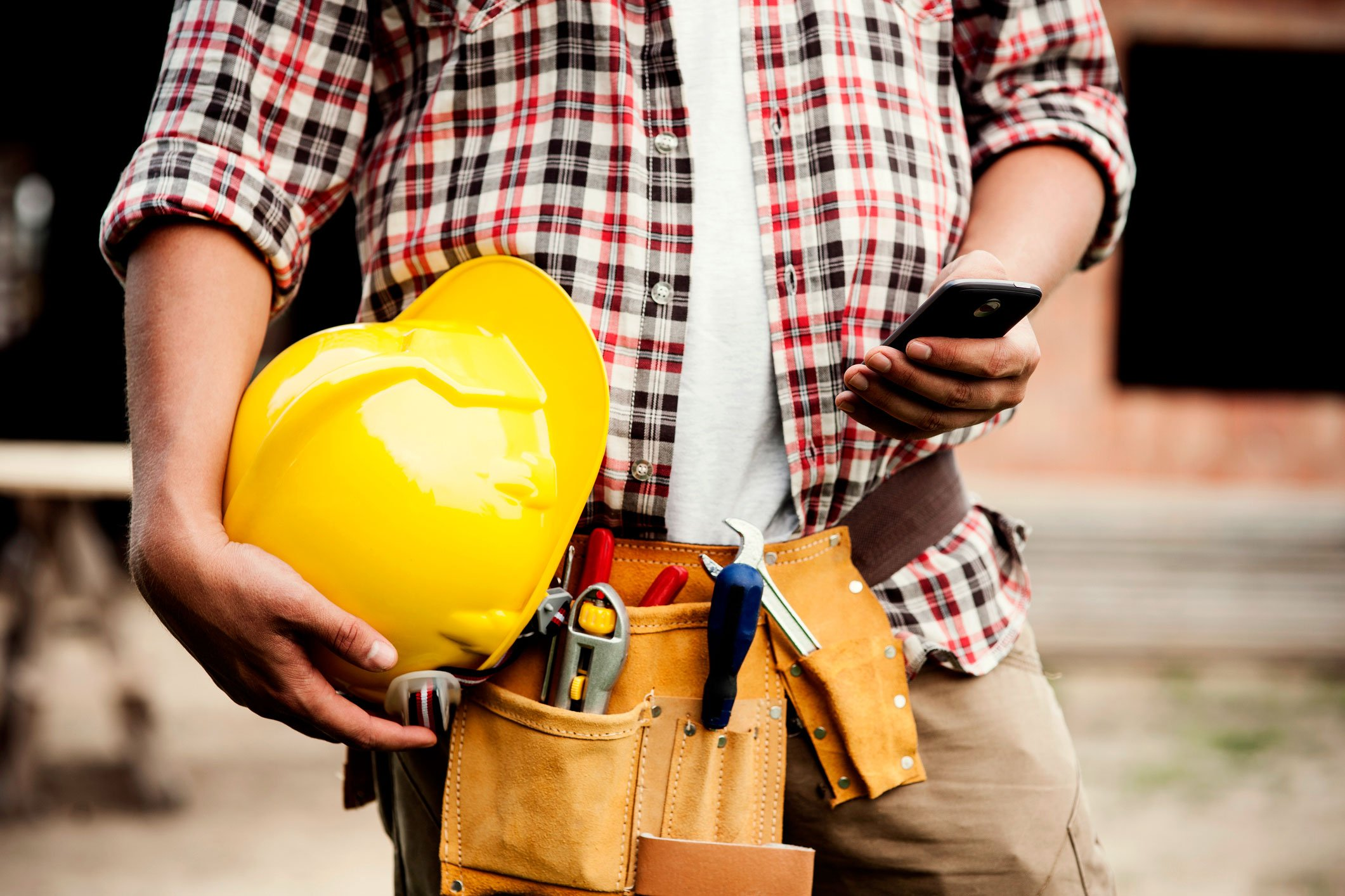 A contractor views smartphone while holding yellow hard hat in right hand